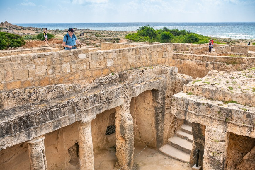 People visiting an ancient ruined building, in front of the sea front
