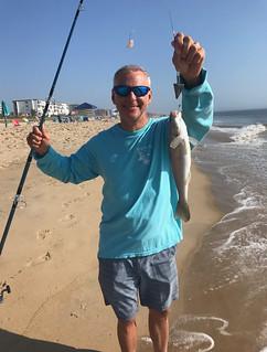 Man holding kingfish on beach