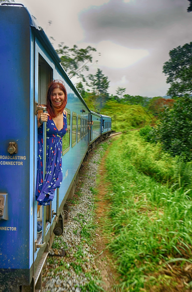 In the left of the photo there is the blue train, with me wearing a blue dress and looking towards the camera. On the right there is green vegetation.
