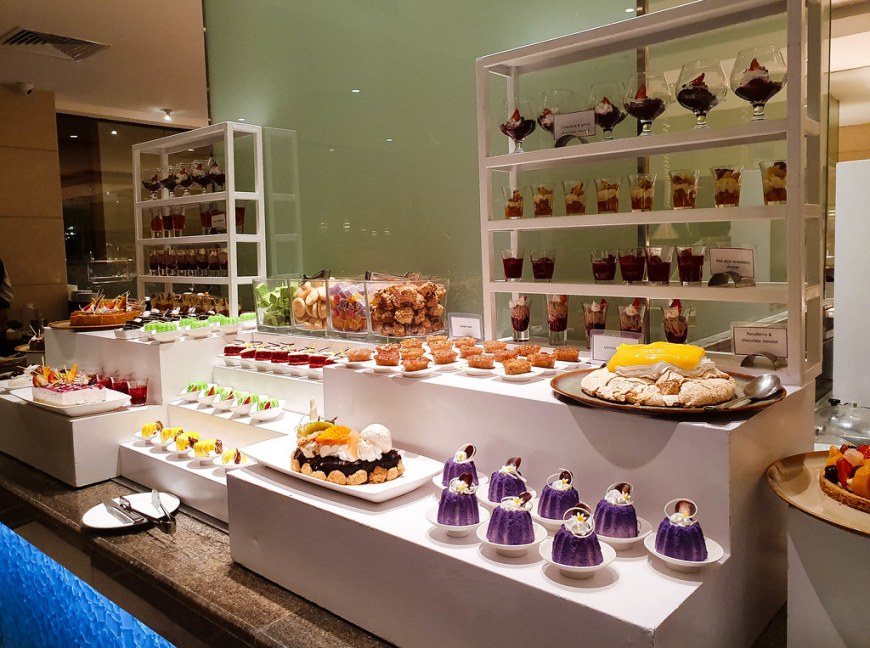 A lot of different cakes, all different colors, arranged on the tables, for dessert
