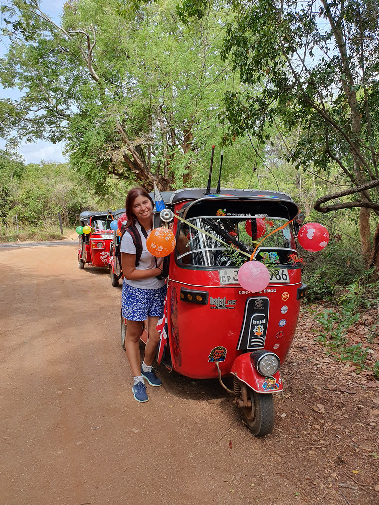 This photo was taken on an unpaved road, surrounded by green trees. I am standing next to a red tuk tuk, which is decorated with red, pink and orange baloons.