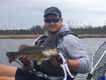 Photo of  man holding a largemouth bass before slipping it back into the water.