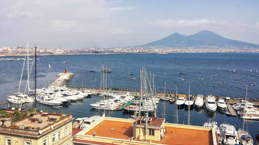 A view of the harbour, with boats in front and the Vesuvius volcano in the background