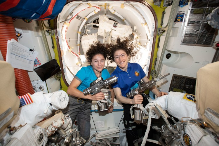 iss061e006501 (Oct. 15, 2019) --- NASA astronauts Jessica Meir (left) and Christina Koch are inside the Quest airlock preparing the U.S. spacesuits and tools they will use on their first spacewalk together. The Expedition 61 flight engineers are holding the pistol grip tools they will use to swap out a failed power controller, also known as a battery charge-discharge unit, that regulates the charge to batteries that collect and distribute power to the International Space Station.