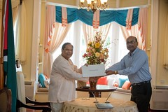 Prime Minister, Hon. Moses Nagamootoo receives the Instrument of Office from Justice Rishi Persaud.