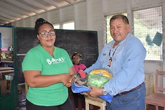 Minister Allicock hands over sports gear to a resident.
