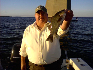 Photo of man with a large white perch at the Bay Bridge.