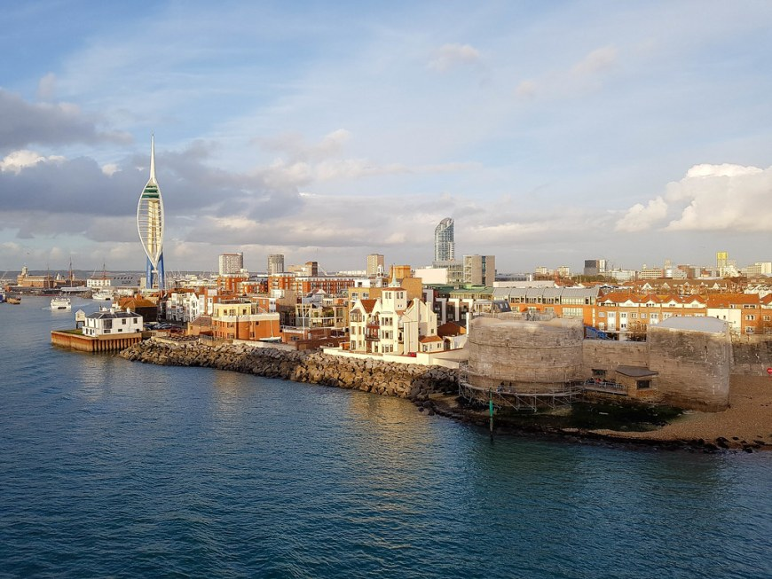 A photo taken at sunrise from a ferry, overlooking the town of Portsmouth. You can see the Spinnaker Tower on the left of the phot and the walls of the old castle on the right. As it is sunset, the light in the photo is warm, with orange shades.