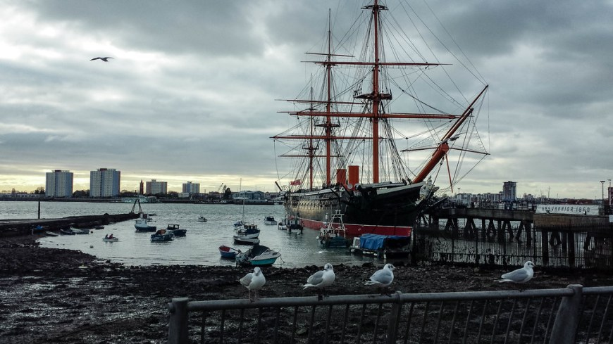 HMS Victory Lord Nelson ship docked into the harbour. The ship is black and has three red masts. The lower part of the ship, touching the water, is red as well. In front of the ship there is a fence on which four seaguls are resting.