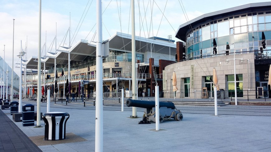 The Gunwharf Keys Shopping centre: two big buildings with a wavy roof, a second floor balcony and many windows around. There are cannons in front of the buildings