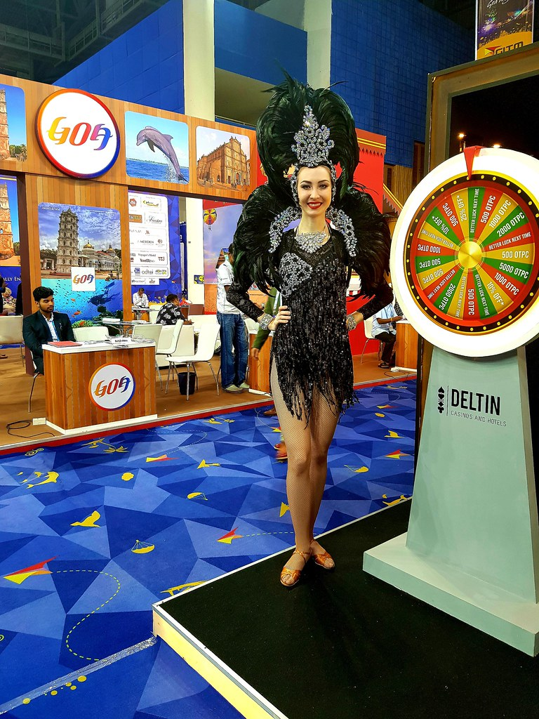 A lady dressed in a black dress with feathers on her head standing near a spinning wheel promoting the Deltin Casinos, during the Goa Travel mart.