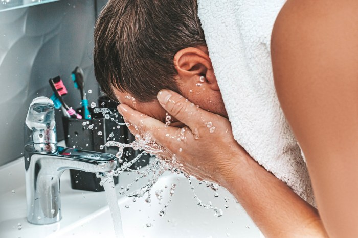 A man washes his face with clean water. The concept of personal hygiene