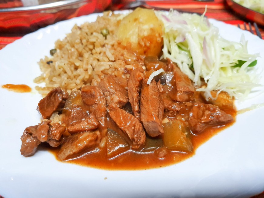 A plate with brown pieces of beef stew covering one third of it, pilau in the left and a white cabbage salad on the right. There is a boiled potato in the middle.