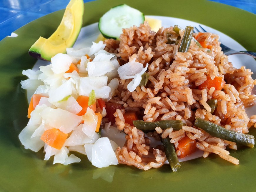 A plate of pilau: red-brownish colored rice, with green beans and carrots inside, next to a white cabbage and carrots salad. In the back of the plate there is a slice of avocado and a slice of cucumber.