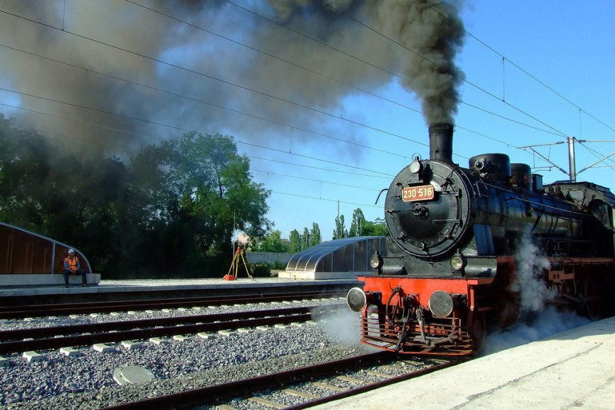 A steam train preparing to leave. There is steam all over the locomotive, whist black smoke is coming out from its chimney
