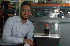 Shiv Outar, the Guyanese offshore technician who tested Guyana's first crude posing with the sample