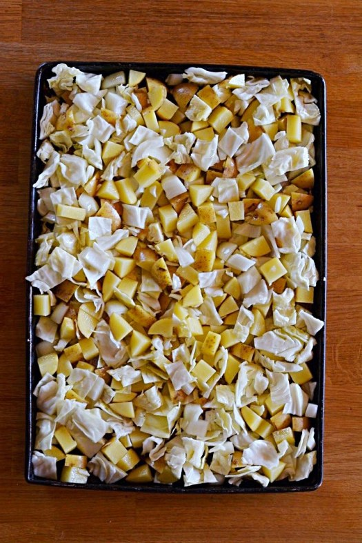 Ingredients on baking tray before going into oven. Cubed yellow potatoes, cabbage and onion tossed with olive oil on a baking tray.