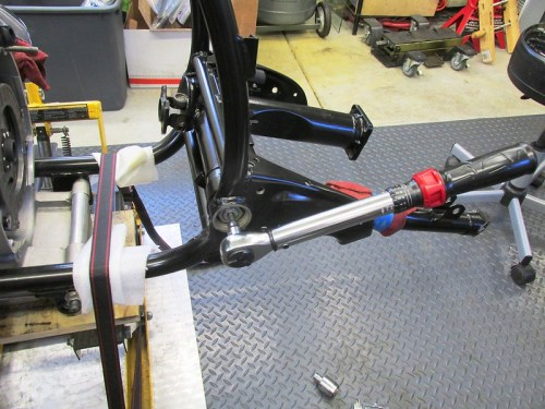 Torque Swing Arm Pivot Bolt To 15 FT-Lbs, Back Off and Set Final Torque To 7.5 FT-Lbs