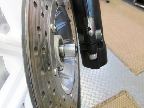 Sliding The Front Axle Through The Front Wheel Left Side Spacer