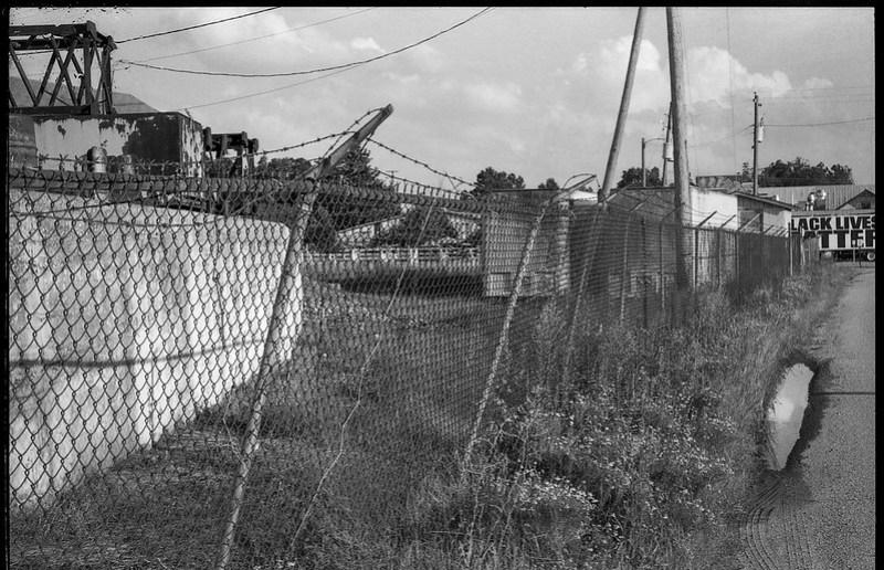 urban landscape, decay, fence, barbed wire, powerlines, puddle, railroad district, Asheville, NC, Minolta XG-M, Fomapan 200, Moersch Eco film developer, 8.1.20