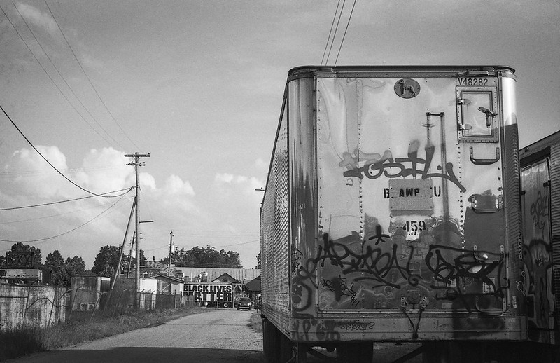 "truck trailer, graffiti, dirt roadway, powerlines, ""Black Lives Matter,"" railroad district, Asheville, NC, Minolta XG-M, Fomapan 200, Moersch Eco film developer, 8.1.20"