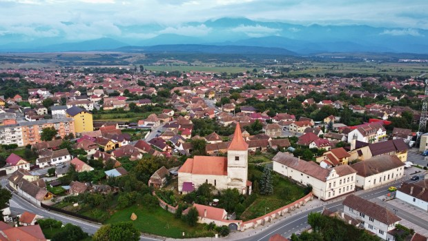 Aerial view of Avrig, with the Evangelical Church and the Carpathian Mountains in the background
