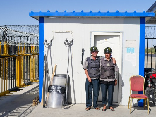 """I spent an hour with this Uighur couple. Nice experience. They didnt give me an easy time when I tried to get into the gas station to buy water (not the simplest task in Xinjiang; see left of picture :-/). But when I came out they invited me into their guard post while I ate my snack, to shelter from the sun.   By chance their boss dropped in to give them their wages. Four twelve hour overnight shifts a week: 2500 RMB between them per month. About £300. They mentioned they have a 22 year old son living nearby. """"Ah, he works locally? No. Ah, then he is looking for work? Er, no."""" My little insight into local job prospects."""