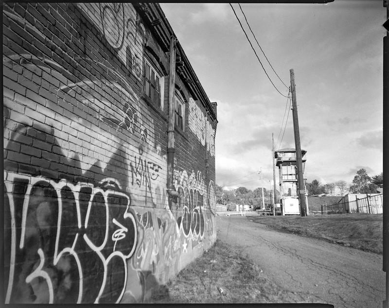 graffitied facade, abandoned mill, brick, distant watchtower and powerline, Asheville, NC, Graflex Crown Graphic, Graflex Optar 90mm f-6.8, Bergger Pancro 400, HC-110 developer, 11.8.20