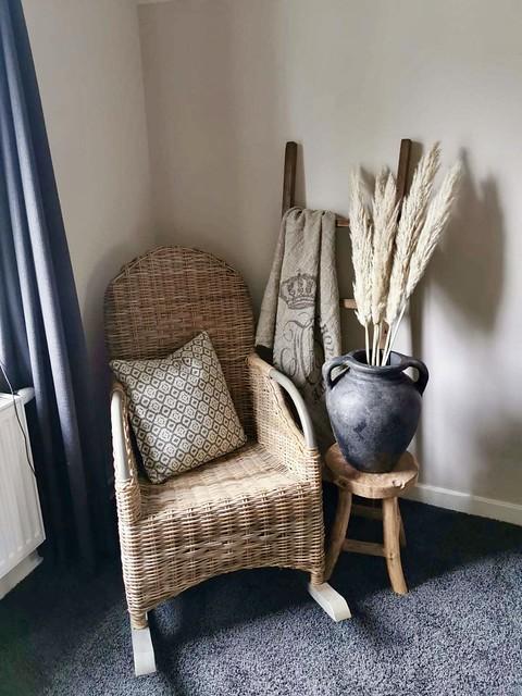 Rotan schommelstoel kruik op krukje pampagras