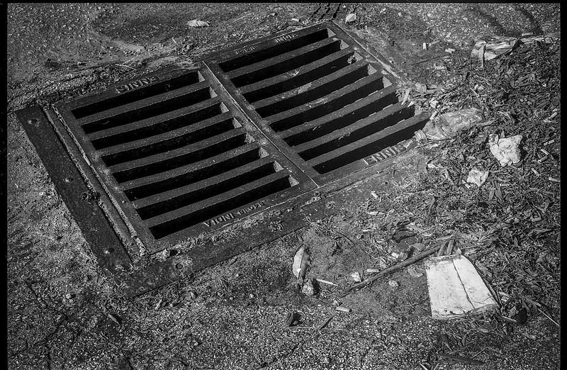 looking down, drainage grate, crumbling pavement, crushed and scattered debris, urban decay, Mister Tire, Patton Avenue, Asheville, NC, Minolta XG-M, Super Albinon 28mm f-2.8, Arista.Edu 200, Moersch Eco developer, 11.24.20