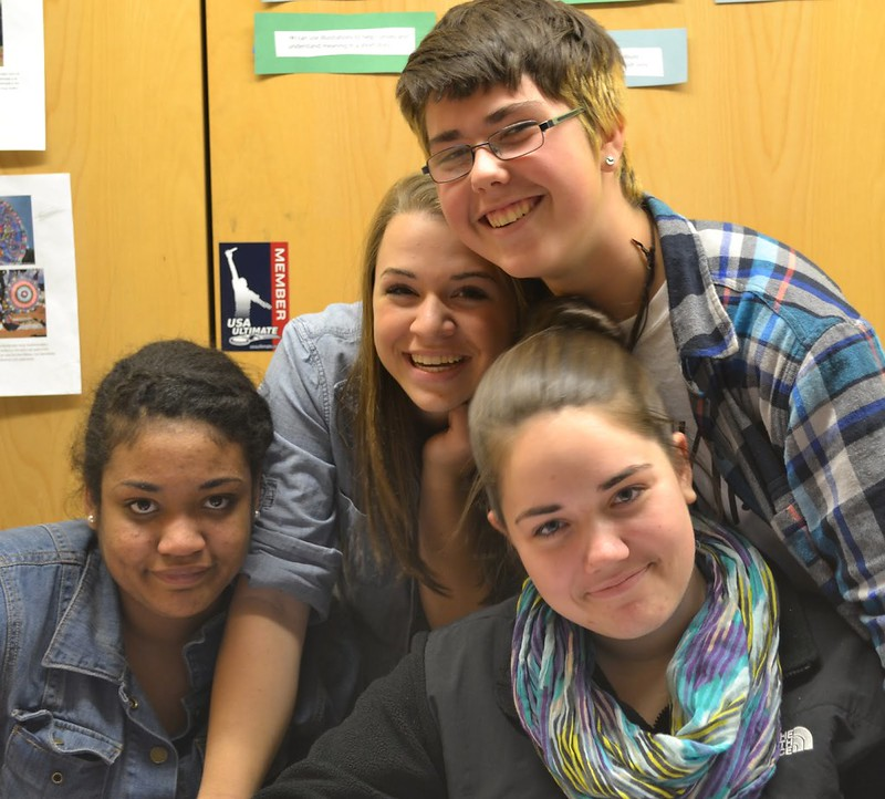 Photograph of teacher with three teenage students smiling for the camera.
