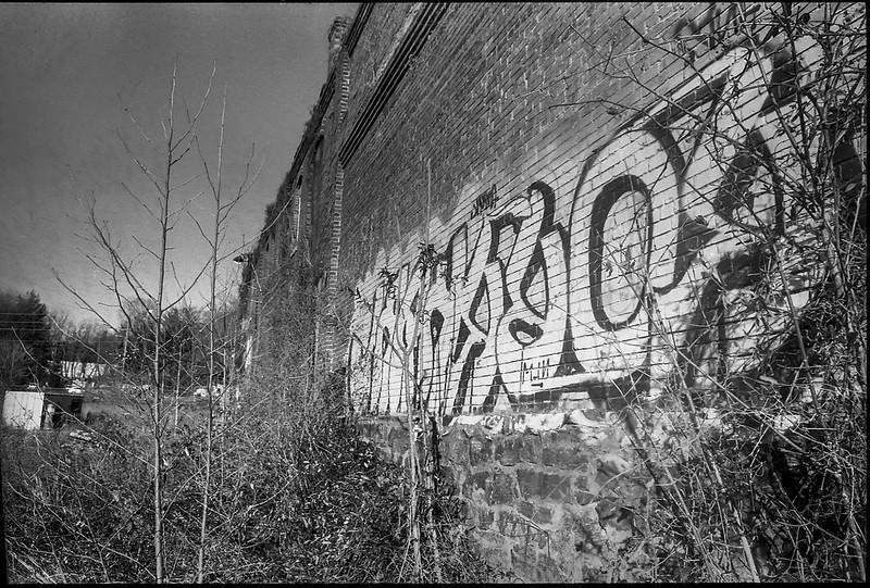 stone and brick facade, abandoned mill, River District, Asheville, NC, Minolta XG-M, Super Albinon 28mm f-2.8, Fomapan 400, HC-110 developer, 1.16.21