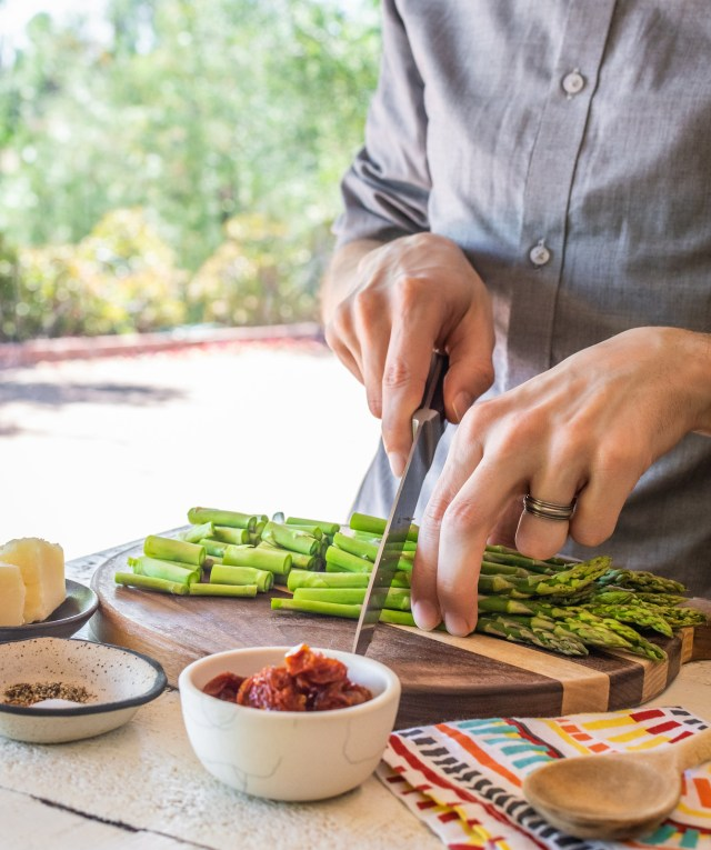 slicing asparagus into bite-sized pieces