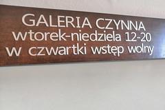 tabliczka na drzwi wejściowe w Galerii Zachęta, litery cięte z aluminium i naklejane na deskę