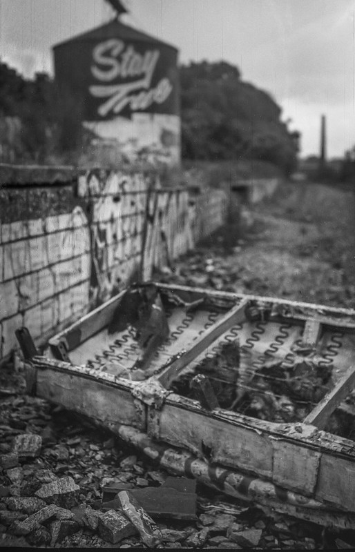"""abandoned and overturned couch, """"Stay True"""" storage silo, graffitied wall, trackside, railroad district,  Asheville, NC, Goerz Pocket Roll Film Tenax camera, Fomapan 200, HC-110 developer, 8.12.21"""