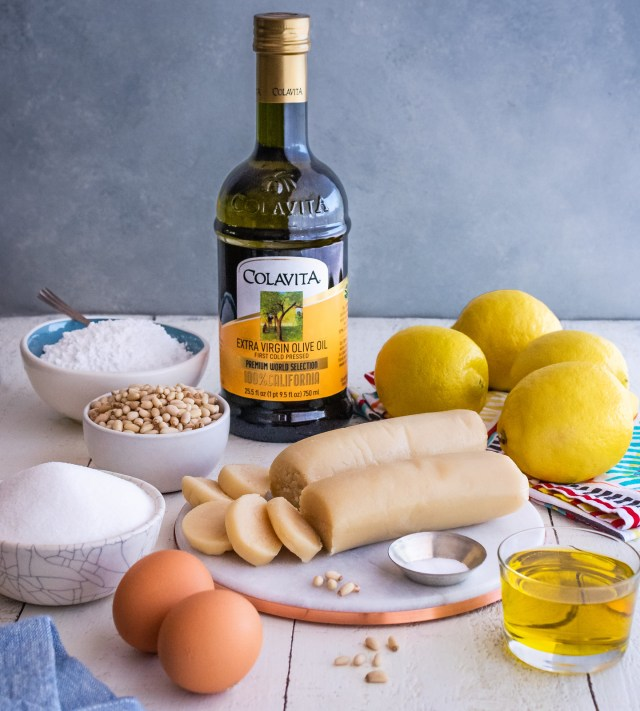 all the ingredients to make pignoli cookies, arranged on a white table