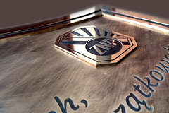 emblemat z log ZNP na tablicy z mosiądzu