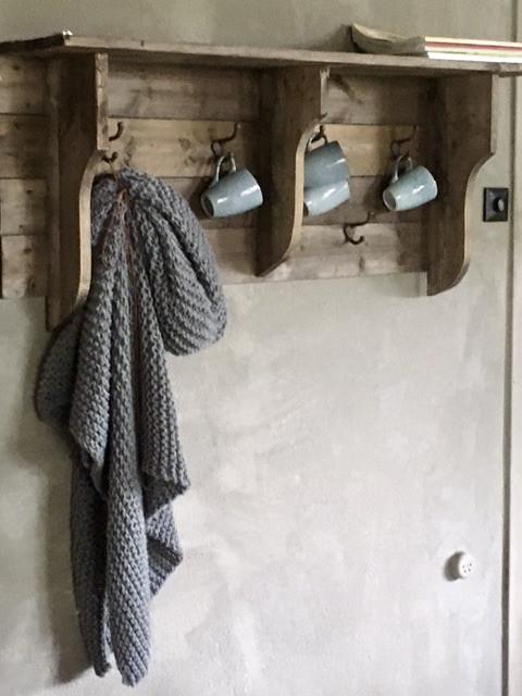Kalkverf muur regaal met grijze bekers gebreide sjaal