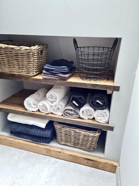 Houten planken nis landelijke badkamer met manden en handdoeken