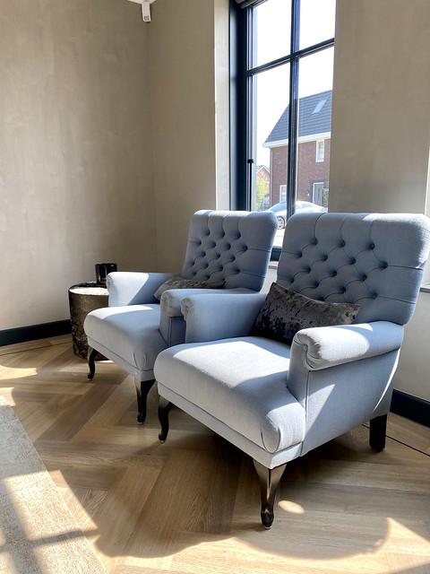 Visgraat vloer landelijke woonkamer grijsblauwe fauteuils zwarte kozijnen