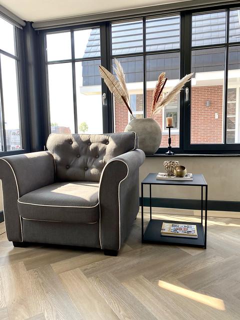 Zwarte kozijnen kruik met pampasgras in vensterbank strak zwarte bijzettafel grijze fauteuil van stof visgraat vloer