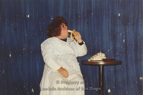 P001.243m.r.t Through The Years Fundraiser: drag queen wearing a white dress eating a banana