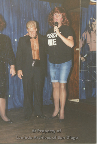 P001.245m.r.t Through The Years Fundraiser: drag queen holding a microphone next to a shirtless man