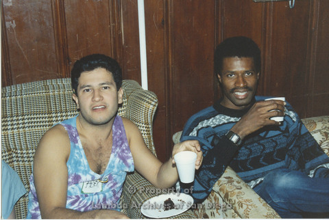 P001.208m.r.t Retreat 1991: 2 men sitting on a couch, one with a nametag (alex) in a tye-dye tank-top