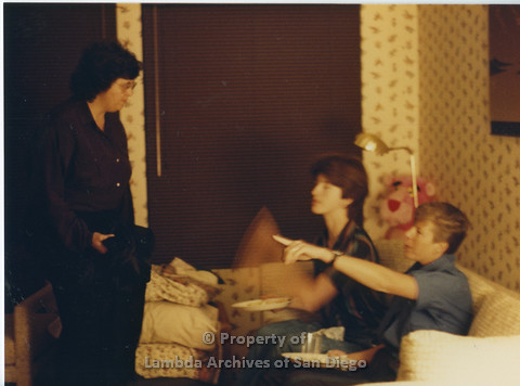 Alix Dobkin Concert, 1985 in the home of Carol Cianfarani: Cory Baca (left) standing in front of Marghi Kilmer (center) and Karen ? (right) on the couch pointing.