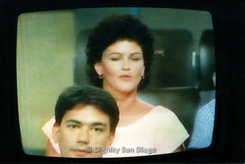 P103.067m.r.t Dignity San Diego: Photo of a woman in peach during a televised AIDS program