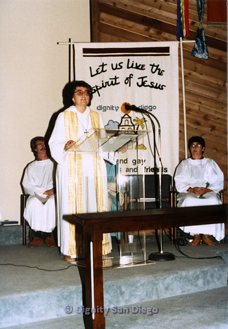 "P103.023m.r.t Dignity San Diego: Female church leader standing in front of banner: ""Let Us Live the Spirit of Jesus Dignity San Diego"""