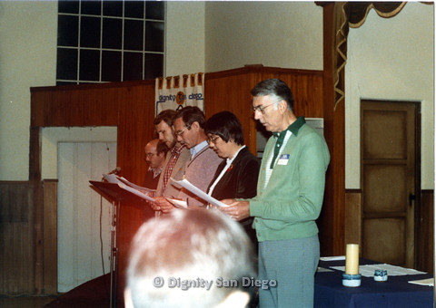 "P103.008m.r.t Dignity San Diego: Four men and a woman reading from papers in front of a congregation, ""Earl"" on right"