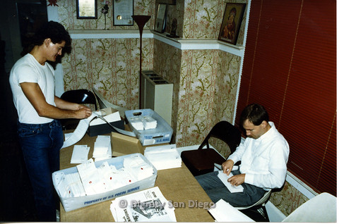 "P103.073m.r.t Dignity San Diego: two men workin on envelopes and sticker addresses, newspaper headline ""DIM: Dignity Center Celebrates Second Anniversary"""
