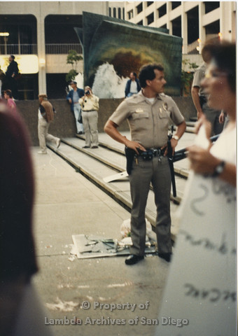 P024.130m.r.t Myth California Protest, San Diego, June 1986: a police officer standing in front of a broken mirror